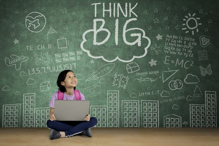 Portrait of a cute schoolgirl looking at word of think big on a chalkboard while studying with a laptop Imagens