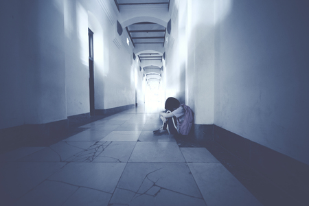Picture of lonely schoolgirl crying and sitting on the floor. Shot in the school corridor