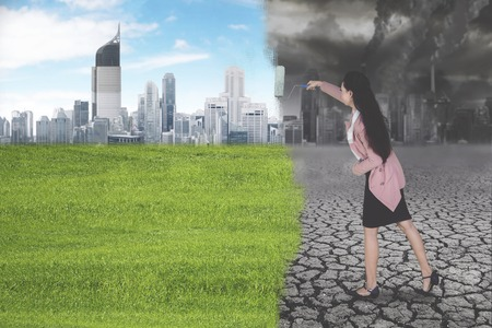Businesswoman holding a roller and transforming the polluted city landscape into green and clean city environment concept
