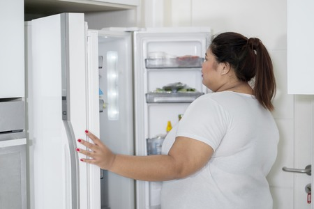 Overweight woman opening a fridge at kitchen
