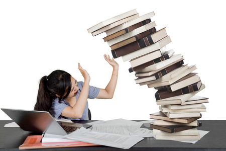 Female student trying to cover her face from falling stack of books isolated over white Foto de archivo