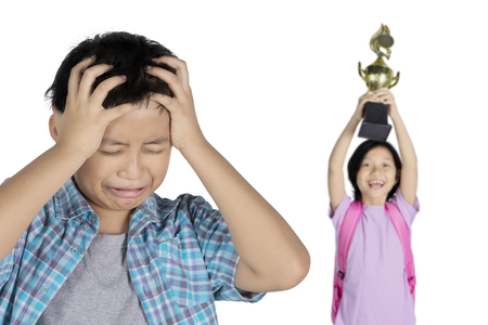 Picture of sad preteen boy looks enviously with his smart sister while standing in the studio, isolated on white background