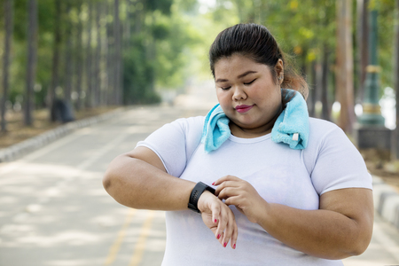 Picture overweight woman wearing her smartwatch before doing a jogging on the road