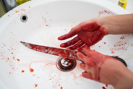 Halloween horror concept. Image of unknown woman hands holding a knife with bloody stain in the sink