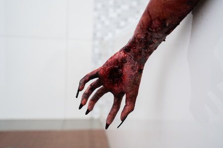 Halloween horror concept. Hand of creepy zombie hand with long nails. Shot in the bathroom 免版税图像