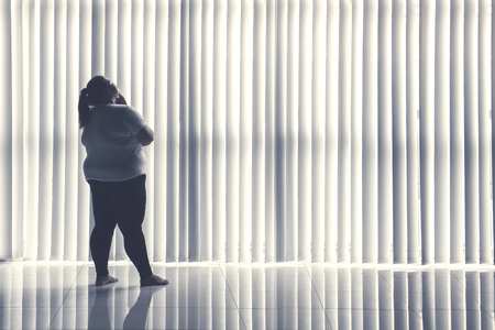 Back view of fat woman daydreaming by the window while standing in the home