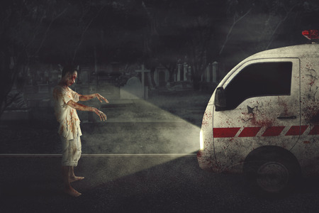 Halloween horror concept. Picture of a creepy zombie man attacking an ambulance car in the grave. Shot at night time