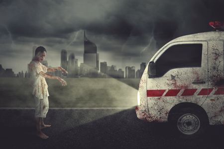 Halloween horror concept. Picture of scary zombie man hindering an ambulance car in the grave. Shot at night time
