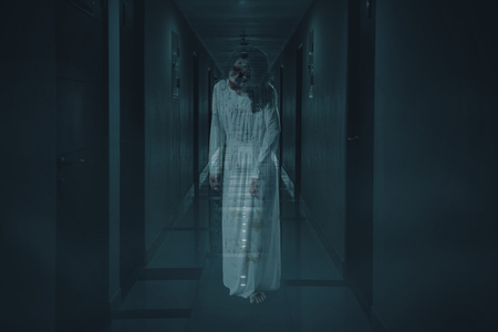 Portrait of scary female ghost walking in the hotel corridor. Concept of Halloween horror