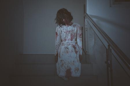 Concepto de horror de Halloween. Imagen de espeluznante fantasma femenino mirando a la cámara mientras está sentado en la escalera. Disparo en casa Foto de archivo