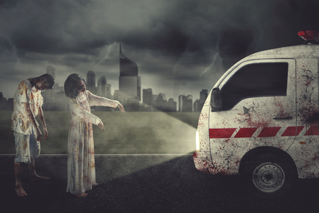 Two creepy zombies stopping an ambulance car while standing with city background at night time. Concept of Halloween horror