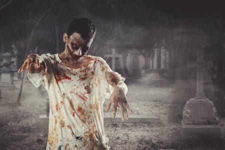 Halloween horror concept. Picture of creepy male ghost walking with wounded face in the grave