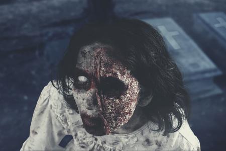Concepto de horror de Halloween. Primer plano de una mujer zombie horrible está mirando a la cámara en el cementerio