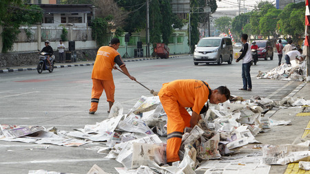 JAKARTA - Indonesia. September 18, 2018: Two sweepers using a broom to sweep the street from rubbish after Eid Al Fitr celebration