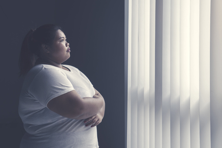 Image of obese woman crossed her hands while daydreaming by the window
