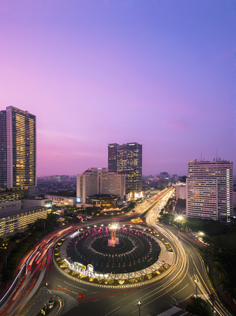 JAKARTA, Indonesia - September 17, 2018: Beautiful aerial view of Hotel Indonesia Roundabout with Grand Hyatt Hotel background and light trail, shot during dusk to night