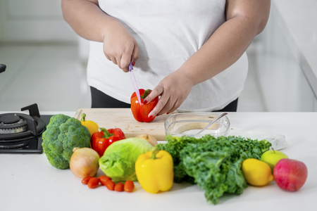 Closeup of unknown woman cutting a paprika while standing in the kitchen Stock Photo