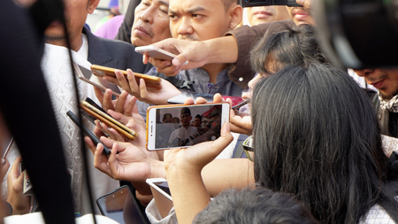 JAKARTA - Indonesia. September 18, 2018: Crowded reporters recording answer from Sandiaga Uno to the question posed
