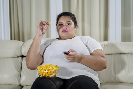 Image of obese woman eating popcorn while watching television in the living room