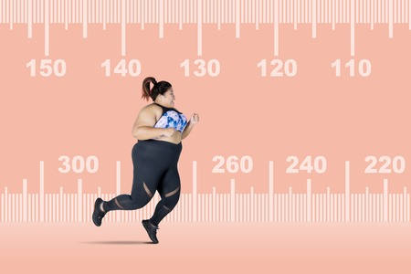 Picture of fat woman looks scared while running with a measure tape background. Concept of lose weight