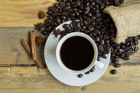 Top view of black coffee with coffee beans, anise, cinnamon, and burlap bag on the wooden table
