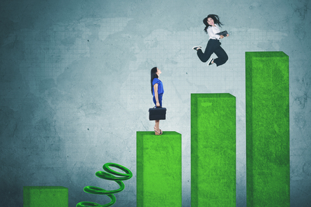 Picture of happy businesswoman jumping over her rival by using big spring above growth chart