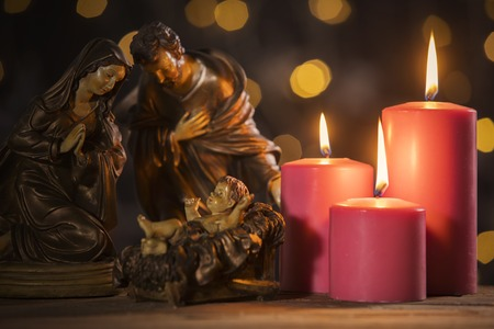 Christmas nativity scene of baby Jesus on the manger with burning candles and blurred sparkling light background Stock Photo