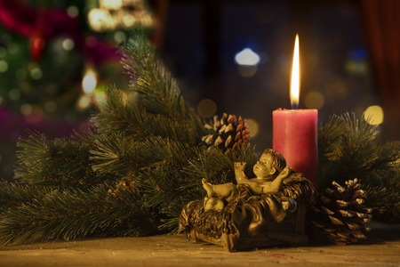 Twigs of the spruce with a baby Jesus statue and burning candle on blurred Christmas tree background