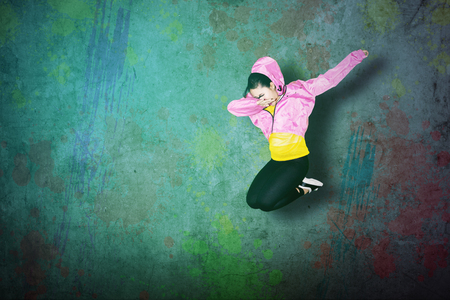 Female hip-hop dancer jumping while making dab dance with colorful concrete background