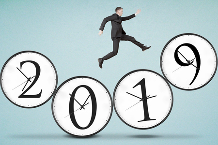 Picture of American businessman running above four clocks shaped number 2019 Imagens
