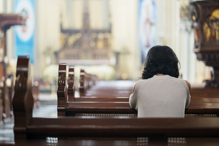 Back view of Christian girl praying to GOD while sitting in the church