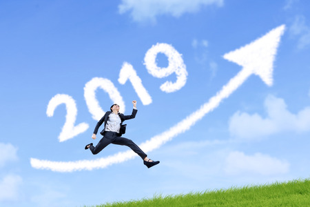 Beautiful businesswoman jumping with clouds shaped number 2019 and arrow upward in the blue sky