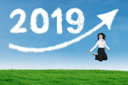 Happy businesswoman celebrating her success by jumps with clouds shaped numbers 2019 and arrow upward in the blue sky Stock Photo