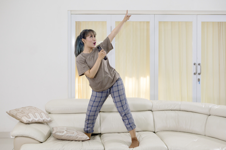 Young woman singing with a remote control while dancing on the couch. Shot at home