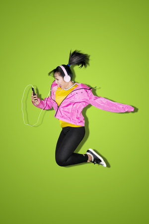 Beautiful female dancer jumping and listening music from her phone in the studio with green screen Stock Photo
