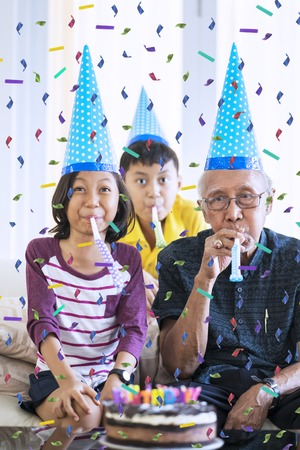 Happy grandchildren celebrating their grandfather birthday while wearing birthday hat with falling confetti at home Stock Photo