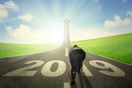 Rear view of fat woman kneeling above number 2019 on the road while running toward toward end road shaped upward arrow