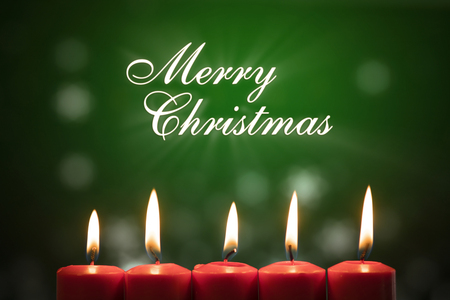 Closeup of five bright candles with Merry Christmas text on green screen background