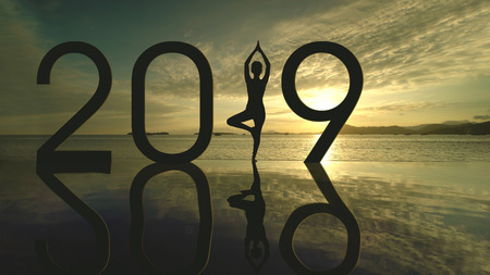 Silhouette of unknown woman exercising yoga on the beach while standing with number 2019 at sunset time Banque d'images