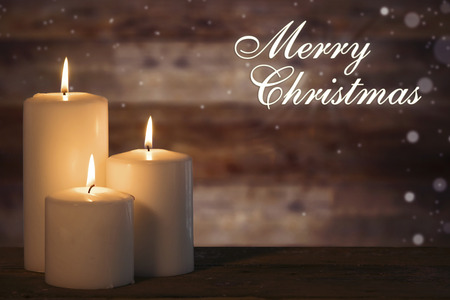 Three white candles burning on the wooden table with Merry Christmas text