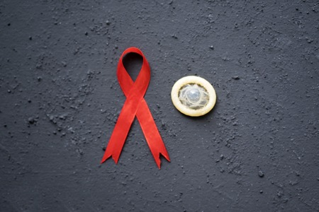 High angle view of a red ribbon with condom on the black table
