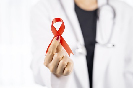 Closeup of a young female doctor showing red ribbon. world AIDS day concept Stock Photo
