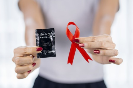 JAKARTA - Indonesia. October 19, 2018: Young woman holding condom and red ribbon in Jakarta, Indonesia