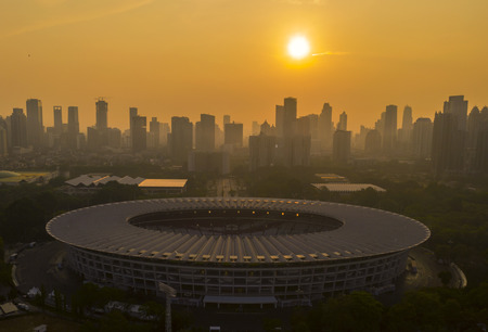 JAKARTA, Indonesia - October 26, 2018: Beautiful aerial view of Senayan soccer field or Gelora Bung Karno stadium at sunset time with silhouette of skyscrapers Редакционное