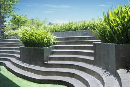 Concrete stairs in the park with green grass and plants under blue sky. Shot outdoors