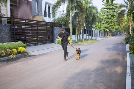 Happy young man running with his German Shepherd dog on the street at the morning