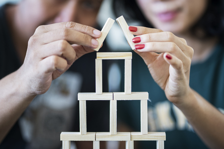 Dream house concept. Young couple playing wooden blocks and making a house shape
