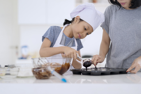 Portrait of cute little girl and her mother preparing chocolate dough on the mold to make cookie in the kitchen at home