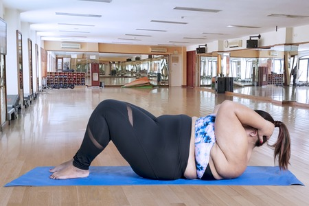 Side view of young fat woman wearing sportswear while doing sit ups in the fitness center