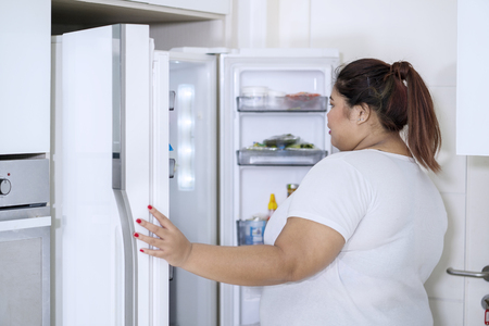 Picture of young fat woman checking foods in refrigerator while standing in the kitchen